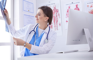 Portrait of doctor sitting in office holding xray image, working on computer