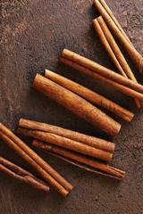 Brown textured background with cinnamon sticks