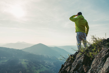 Adventurous man is standing on top of the mountain and enjoying the beautiful view during a vibrant sunset. Fototapete
