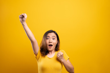 Happy woman make winning gesture isolated over yellow background Wall mural