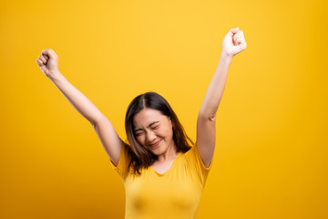 Happy woman make winning gesture isolated over yellow background Fototapete