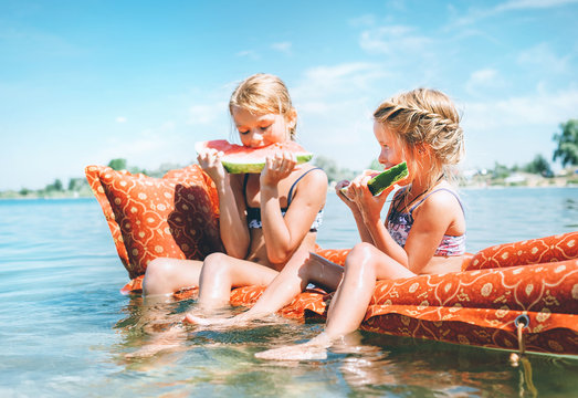 Two little sisters sitting on innflatable mattrace and eating watermelon