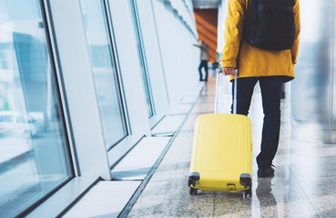 Fototapeta traveler tourist with yellow suitcase backpack at airport on background window blue sky, man waiting in departure area, hall of airport lobby terminal, vacation trip concept, empty space mockup obraz