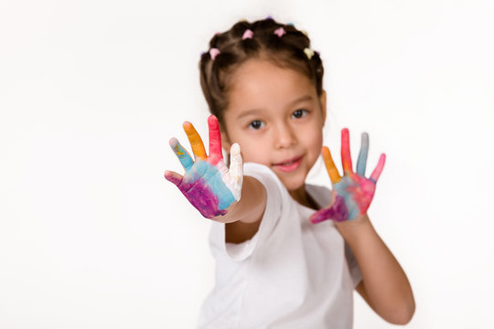 cute little child girl with hands painted in colorful paint shows stop gesture isolated on white background.