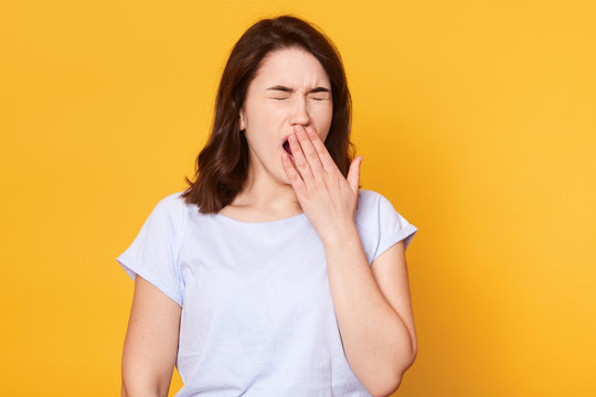 Beautiful woman yawns isolated over yellow background, wears casual white t shirt, has wavy hair, keeps hand near mouth. Free space for advertisment or promotional text. People and lifestyle concept.