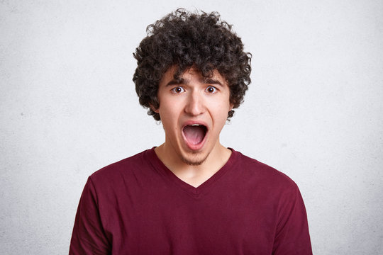 Portrait of shocked young man in casual clothes keeping mouth wide open, stands isolated on white wall background in studio. People, emotions and lifestyle concept. Copy space for promotion.