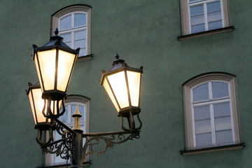 Old street lights in the night and green building at background on Krakow (Poland)