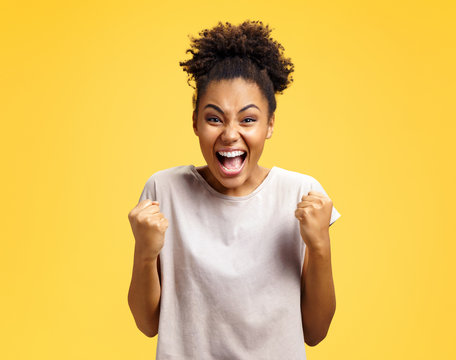 Excited girl with widely open mouth holds hands clenched in fists, exclaimed with positiveness. Photo of african american girl on yellow background. Emotions and pleasant feelings concept.