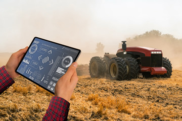 Wall Mural - A farmer with digital tablet controls an autonomous tractor on a smart farm