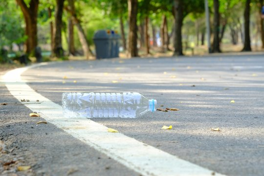 A bottle of drinking water littering on a road ground floor at the green park with blurred a trash bin in the sideway for an environmental cleaning concept