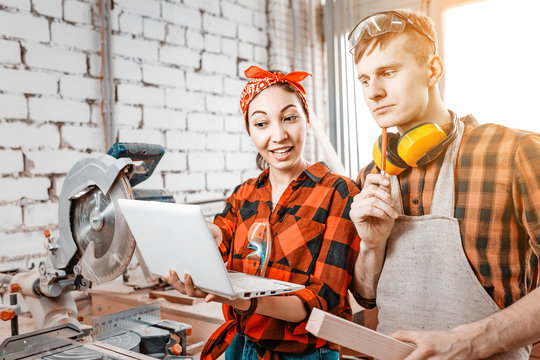 A man and a woman colleagues communicate and look at the laptop in the industrial workshop at the plant. The concept of modern technological production and teamwork