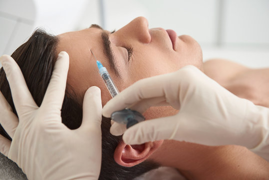Man on beauty injection procedure of forehead skin