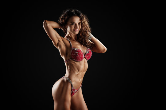 Athletic woman in red bikini showing muscles on dark background. Copy space