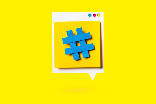 Paper cutout of hashtag symbol on a yellow speech bubble on yellow background. Concept of social media and digital marketing.