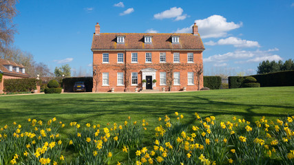 Fototapeta Elegant English Country Manor mansion house Grade 2 listed Victorian period property in red brick. Front view with large garden, green lawn and daffodils obraz