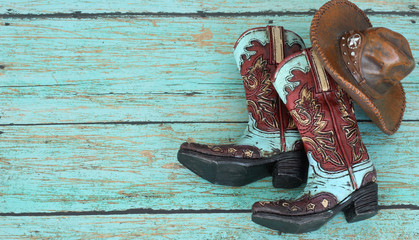 cowboy boots and hat laying on a teal background Wall mural