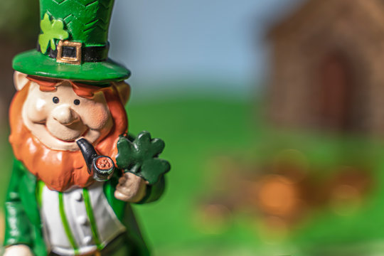 A happy leprechan in the forest in front of his gold.