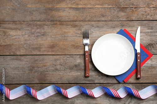 Patriotic table setting with traditional USA colors on wooden background, flat lay. Space for text