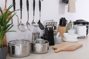 Obraz Set of clean cookware, dishes, utensils and appliances on table at white wall - fototapety do salonu