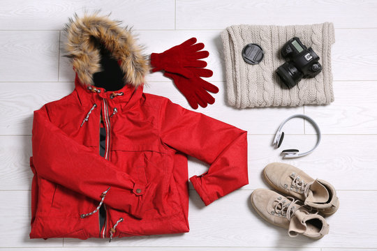 Flat lay composition with warm clothes for winter vacation on wooden background