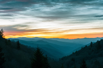 Orange glow from the sun illuminates the sky over the Great Smoky Mountains