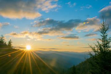 Morning sunrise over the Oconaluftee Valley in the Great Smoky Mountains National Park with bright sun rays.
