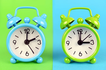 Concept of change from winter to summer time. Blue and green  retro alarm clock on colorful background.