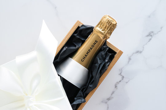 A champagne bottle and a gift box on marble