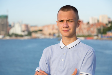 Portrait of a young guy on the background of the sea and city