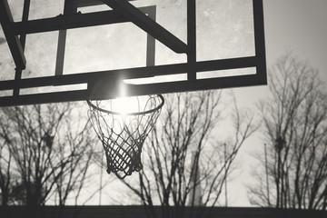 Monochrome image of old basketball backboard and sun inside the rim
