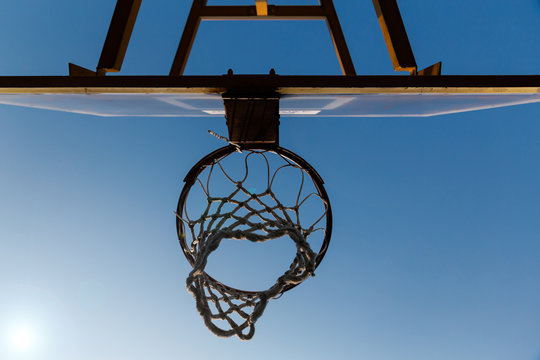 Bottom view of old basketball hoop and clear blue sky