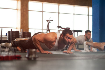 Small Group of Muscular Male Adults Warming Up Training Push Ups.