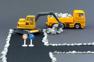 Diorama road construction with yellow construction machinery models. Construction concept. Children's toys of construction machinery. Closed road with no entry. Excavator loads stones on truck.
