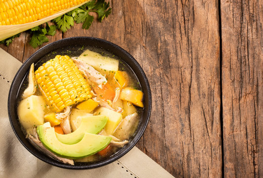 Colombian cuisine: ajiaco soup with chicken and vegetables close up in a bowl.
