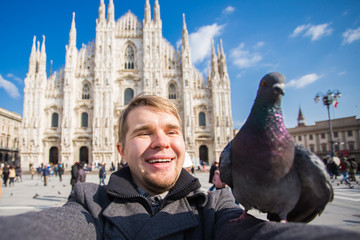 Winter travel, vacations and birds concept - Handsome male tourist with funny pigeons making selfie photo in front of the famous Duomo cathedral in Milan.