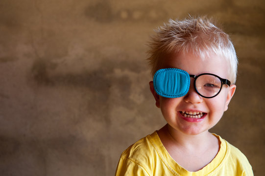 Portrait of funny child in new glasses with patch for correcting squint .Ortopad Boys Eye Patches nozzle for glasses for treatment of strabismus (lazy eye)