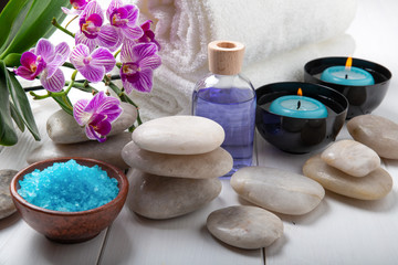 composition of the spa treatment. Candles in bowls with water, bath salts, and orchid flowers.