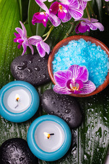 bowl with lavender-scented bath salt, orchid, massage stones, covered with water drops, and scented candles.