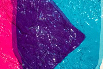 Thin sheet of multi coloured cellophane with shiny crumpled surface texture,  Abstract background, Light & Shadow concept