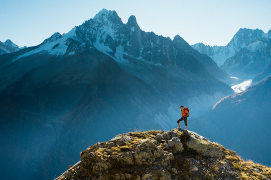 A hiker on top of a rocky summit in the mountains of the Alps