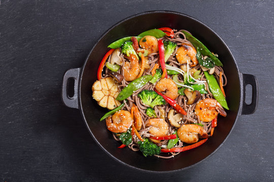Stir fried noodles with shrimps and vegetables in a wok, top view