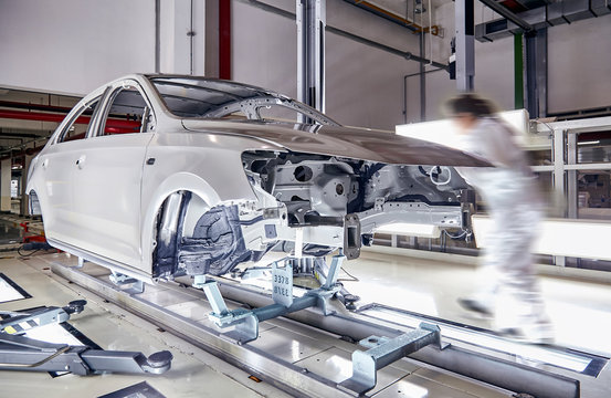 The robots in the car manufacturing plant are helping the car body to be glued at the seams.
