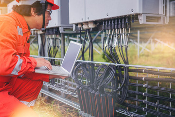 Electrical and instrument technician use touch pad for guide to maintenance electric system at electric solar plant