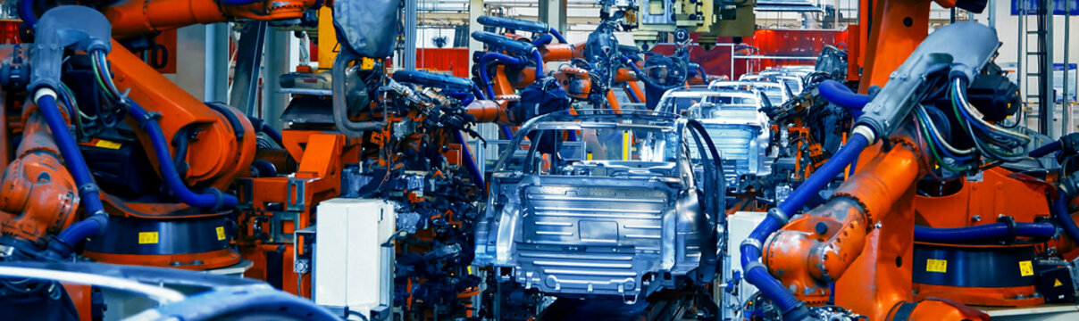 The automated robotic arm in the car manufacturing plant is busy working on the assembly line.