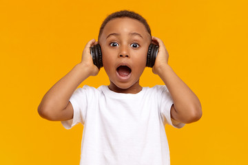 Genuine human facial expressions, emotions and modern gadgets. Emotional funny African child in white t-shirt opening mouth widely, demonstrating full disbelief, wearing black wireless headphones Fototapete