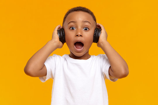 Genuine human facial expressions, emotions and modern gadgets. Emotional funny African child in white t-shirt opening mouth widely, demonstrating full disbelief, wearing black wireless headphones
