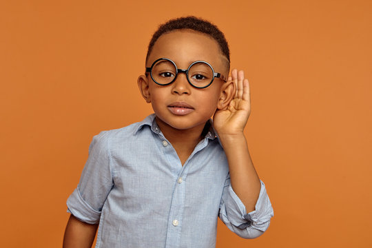 Studio shot of stylish curious snoopy Afro American schoolboy in trendy eyewear holding hand at his ear, trying to overhear private conversation, posing at orange blank wall. Body language