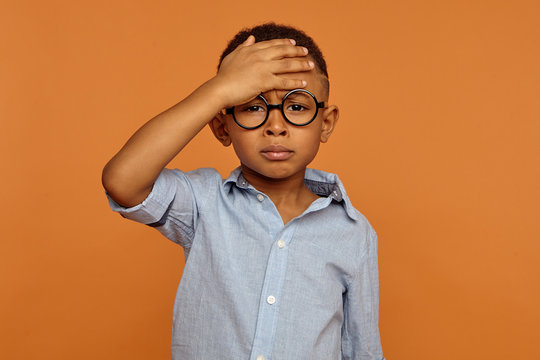 Sad unhappy African American schoolboy in trendy eyewear having painful look, holding hand on his forehead after he fell. Frustrated sick dark skinned child suffering form terrible headache