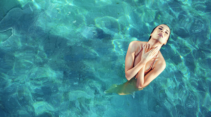 Young, sensual woman realxing in a clear, tropical water
