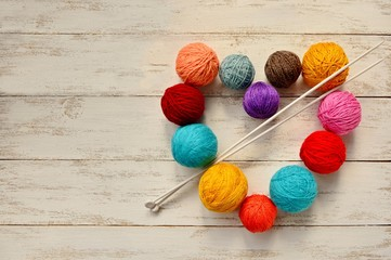 Balls of multicolored yarn heart-shaped and knitting needles on white wooden background.